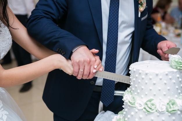 結婚披露宴での新郎新婦おいしいウエディングケーキを切る。伝統的