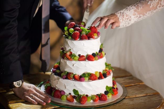 結婚披露宴で新郎新婦がウェディングケーキを切る