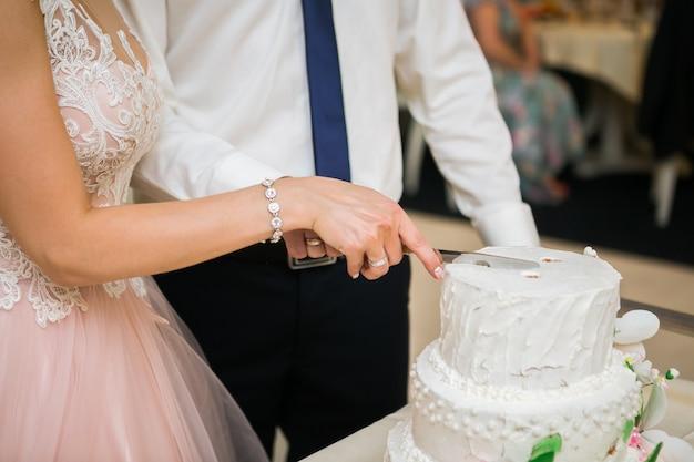 結婚披露宴で新郎新婦が白いウエディングケーキを切る