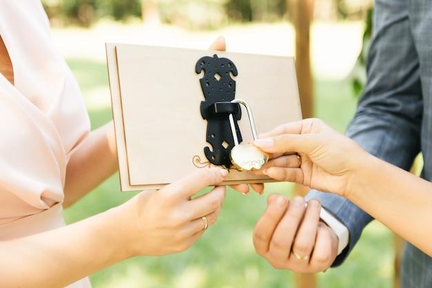 Жених и невеста закрывают замок на счастье