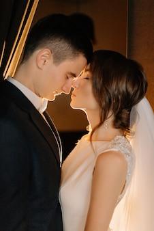 Жених и невеста крупным планом портрет в день свадьбы. молодожены с закрытыми глазами касаются друг друга носами. свадьба, любовь, концепция отношений. низкий ключ.