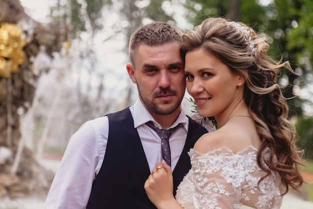 花嫁と花婿は、背景に噴水がある公園を抱きしめるスタンドをクローズアップ