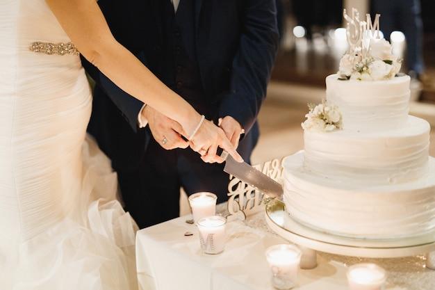 白いフロスティングで3段ケーキを切る新郎新婦