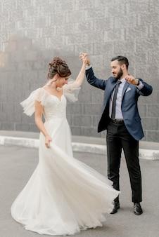 Жених и невеста танцуют на улице
