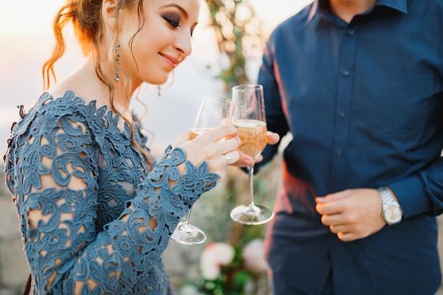 Жених и невеста пьют шампанское из бокалов возле свадебной арки во время свадебной церемонии