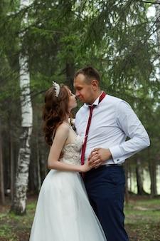 新郎新婦は、太陽の下で暗い森の中で抱き合ってキスします。自然の中での結婚式、公園で恋をしているカップルの肖像画