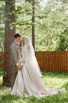 Жених и невеста обнимаются, красивая свадьба на природе. любящая молодая пара
