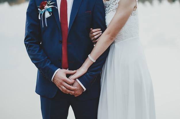신부와 신랑은 서로 포옹합니다. 파란색 남성 의상 wth 진한 빨간색 넥타이와 흰색 레이스 쉬폰 드레스.