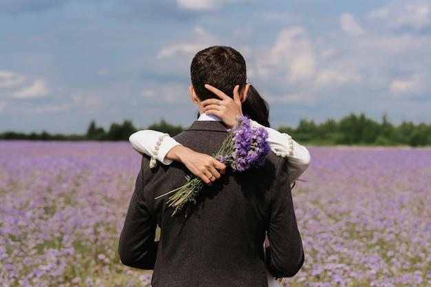 Жених и невеста обнимаются в поле летних цветов в день свадьбы