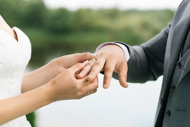 Жених и невеста обмениваются кольцами крупным планом