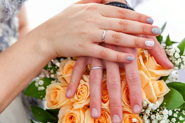 Руки жениха и невесты с обручальными кольцами на фоне свадебного букета цветов.