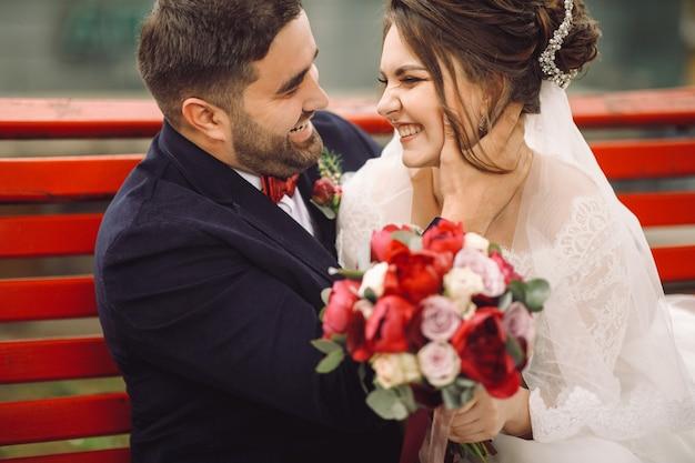 花嫁と新郎は楽しい外にベンチで抱擁とキスをしている
