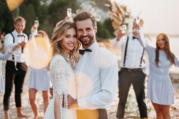 ビーチでゲストと結婚式をする新郎新婦