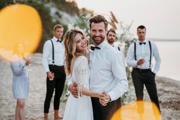 ビーチでゲストと結婚式をする新郎新婦 無料写真