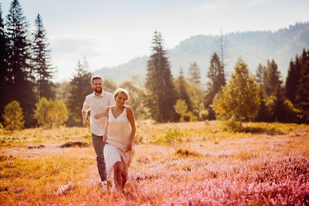 花嫁と新郎は、フィールドを渡って走っている互いの手を保持する