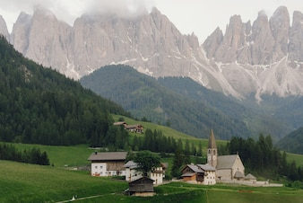 Bride and groom hold each other hands walking to the church somewhere in Italian Dolomites