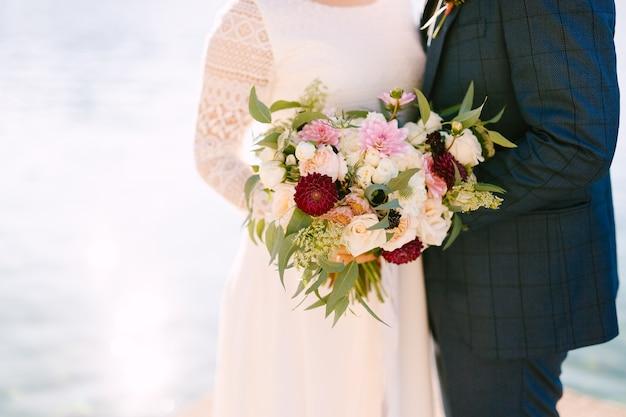 花の美しい花束を保持している新郎新婦