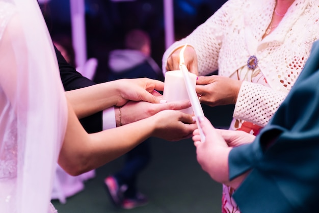 Невеста и жених, держа свечу. традиция возгорания семейного очага