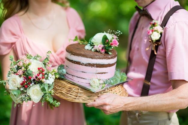 Жених и невеста держат деревенский свадебный торт