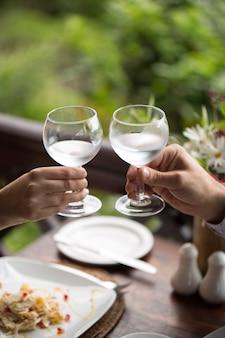 美しく装飾された結婚式のガラスを保持している新郎新婦