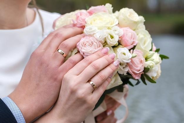 バラのブライダルブーケを一緒に保持している新郎新婦。結婚指輪は指にあります。