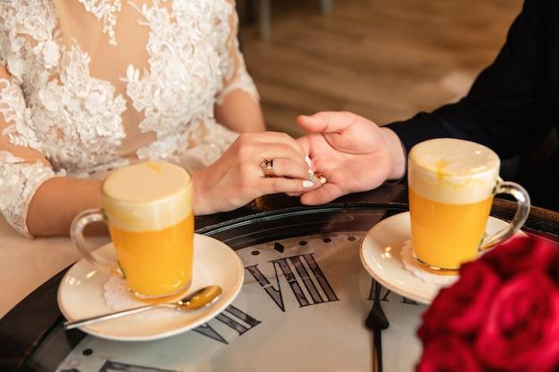 노란색 칵테일 근처 시계와 테이블에 손을 잡고 신랑과 신부