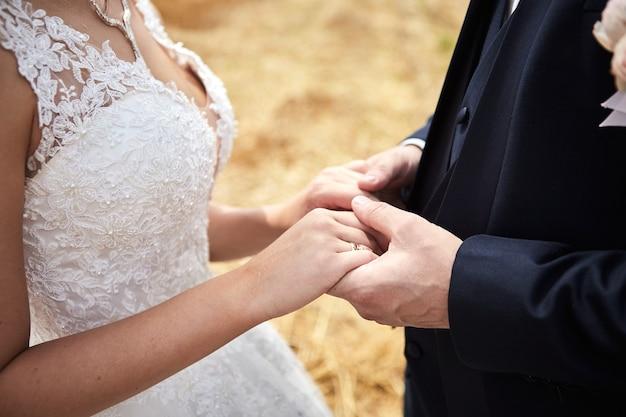 Жених и невеста, взявшись за руки на открытом воздухе, свадебная тема