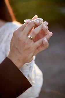 Жених и невеста, взявшись за руки на открытом воздухе