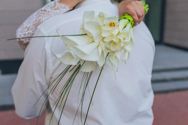 結婚指輪と花嫁の花束の詳細を手に持っている新郎新婦