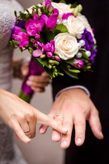 花束と手をつないで新郎新婦