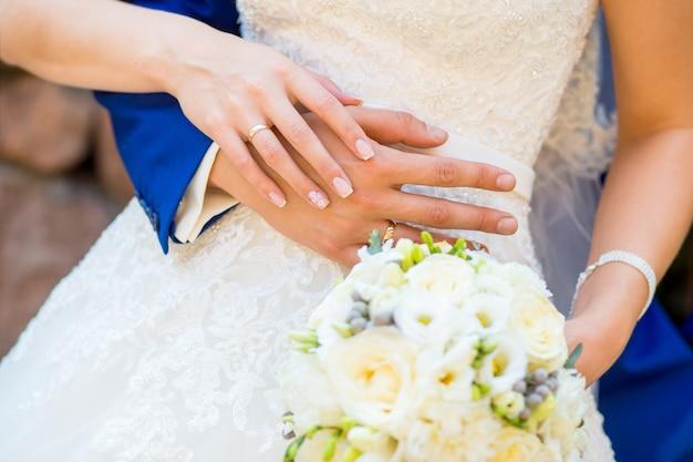 Жених и невеста, взявшись за руки с букетом