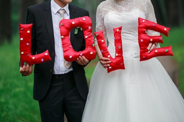愛という言葉を保持している新郎新婦をクローズアップ。聖バレンタインの日の壁。手作りの布文字で構成される碑文愛。結婚式の日。ロマンチックな瞬間