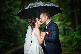 花嫁、新郎、キス、笑顔、お互いを見て、手に傘を持つ