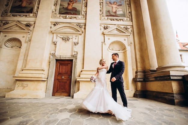 新郎新婦の抱擁、結婚式の日に屋外でキス、若いカップルがプラハを歩く、バレンタインデー