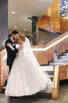 結婚式の日に抱き合ったりキスしたりする新郎新婦。新しい家族、恋をしている幸せなカップル、男性と女性がお互いを愛し合っています。結婚式。白いウェディングドレスの花嫁