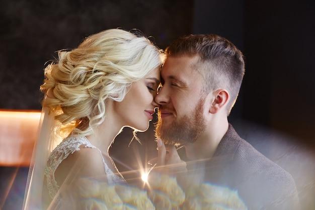 結婚式の日に抱き合ったりキスしたりする新郎新婦は焦点を合わせていません。新しい家族、恋をしている幸せなカップル、男性と女性がお互いを愛し合っています。結婚式。白いウェディングドレスの花嫁
