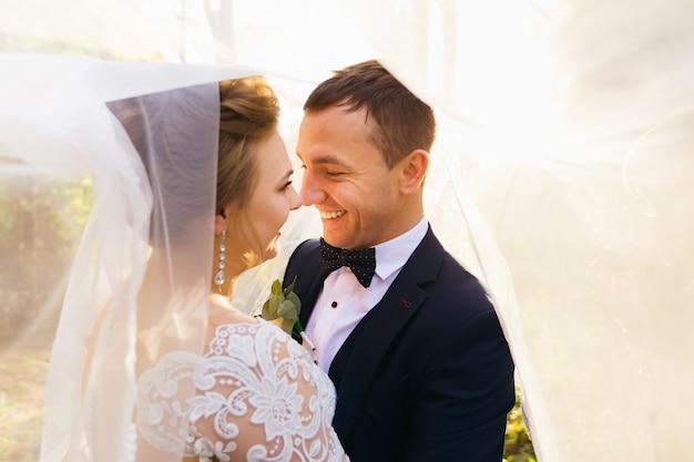 公園で新婚夫婦の結婚式のベールの下で抱き合って見つめ合う新郎新婦