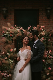 Жених и невеста обнимаются возле свадебной арки