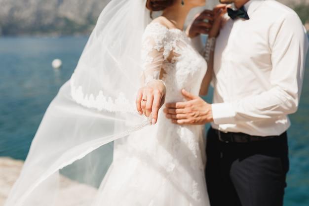 Жених и невеста обнимаются на пирсе в которской бухте