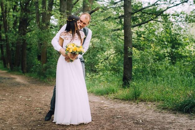 Жених и невеста обнимаются в день свадьбы, счастливая молодая пара целуется в парке на природе, день святого валентина