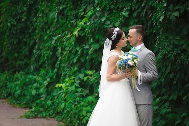 公園でキスをしている新郎新婦。自然の緑の森での結婚式でカップルの新婚の花嫁と花婿が写真の肖像画にキスしています。結婚式のカップル