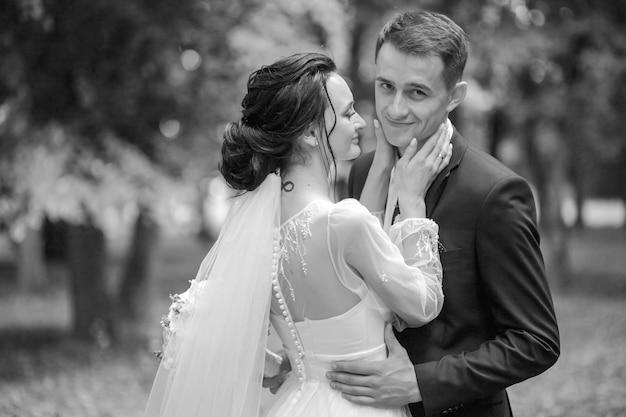 自然の緑の前での結婚式で新婚夫婦の新婚の花嫁と花婿をキスする公園の新郎新婦