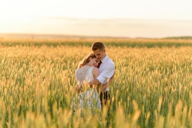 Жених и невеста в пшеничном поле. пара обнимает во время заката.