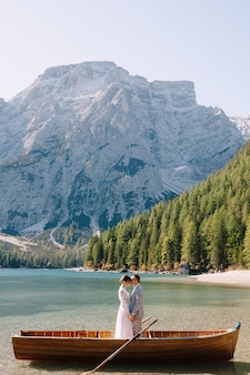 Жених и невеста в деревянной лодке на озере брайес в италии. свадебная пара в европе, на озере брайес, в доломитовых альпах