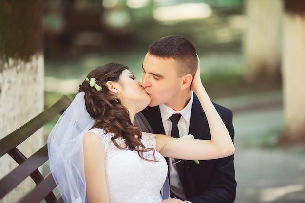 Жених и невеста в ярких одеждах на скамейке