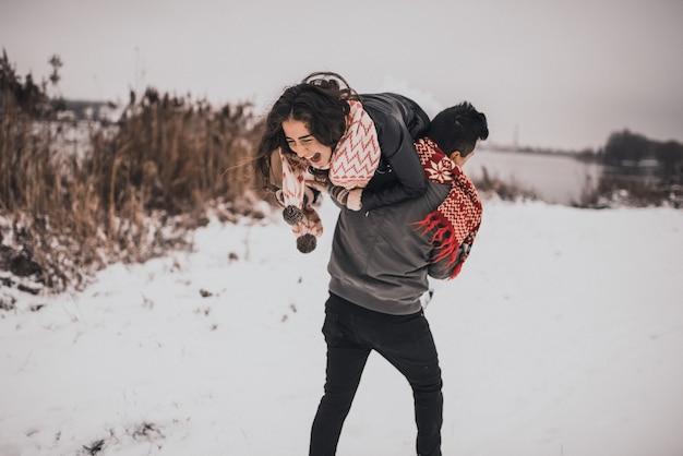 冬と雪片のニットスカーフミトンの愛のカップルの新郎新婦