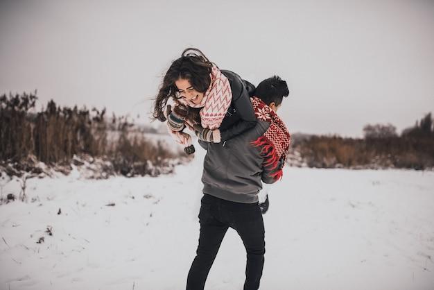 Влюбленная пара жениха и невесты в вязаном шарфе и зимних рукавицах