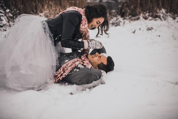Влюбленная пара жениха и невесты в вязаном шарфе варежках зимой и снежинках