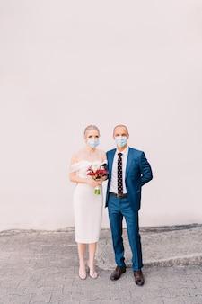 灰色の背景に医療マスクの新郎新婦。隔離中の2人の結婚式、covid-19