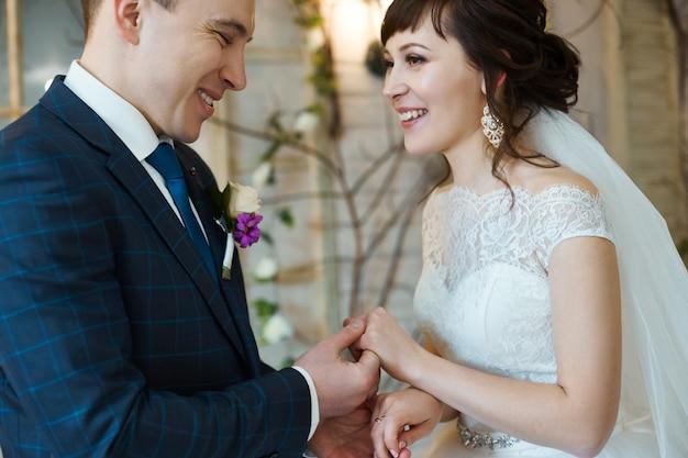 Жених и невеста в свадебной одежде обнимаются дома. влюбленная пара после свадебной церемонии